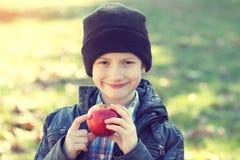 Piccola mela della tenuta dello scolaro dei pantaloni a vita bassa Immagine Stock Libera da Diritti