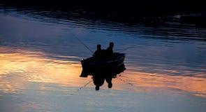 Piccola nave dei pescatori su un lago del tramonto fotografia stock