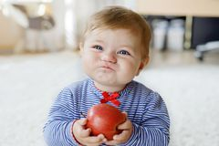 Piccola neonata adorabile che mangia grande mela rossa Vitamina ed alimento sano per i piccoli bambini Ritratto di bello bambino fotografia stock