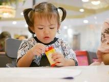 Piccola neonata asiatica che impara aprire il contenitore di pastello sola fotografie stock