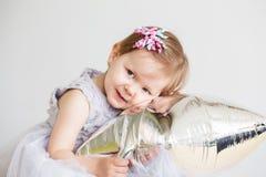 Piccola neonata che gioca con il pallone a forma di stella d'argento Immagini Stock