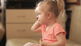 Piccola neonata che gioca con il telefono all'interno colpo 4k video d archivio