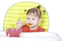 Piccola neonata che mangia una purea di vegetali Immagini Stock