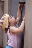 Piccola neonata che raggiunge per un perno di portello Fotografia Stock