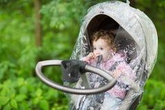 Piccola neonata che si siede in un passeggiatore nell'ambito di una copertura della pioggia Immagine Stock