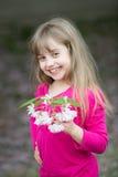 Piccola neonata con il fronte sorridente che tiene il fiore rosa di sakura fotografia stock libera da diritti