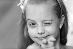 Piccola neonata con sbattere le palpebre sorridente del fronte all'aperto Fotografia Stock