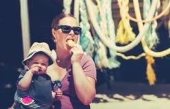 Piccola neonata con sua madre sulla spiaggia che mangia ghiaccio fotografia stock libera da diritti