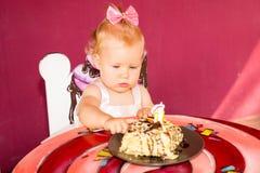 Piccola neonata felice che celebra primo compleanno Bambino ed il suo primo dolce sul partito Infanzia Fotografie Stock Libere da Diritti