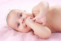Piccola neonata felice che si trova con la mano in bocca Fotografia Stock