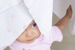 Piccola neonata felice nascosta il suo fronte in pannolino bianco del panno Fotografie Stock Libere da Diritti