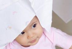 Piccola neonata felice nascosta il suo fronte in pannolino bianco del panno Fotografia Stock