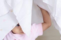 Piccola neonata felice nascosta il suo fronte in pannolino bianco del panno Immagine Stock Libera da Diritti
