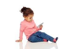 Piccola neonata sorridente che gioca con lo smartphone Fotografie Stock