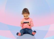 Piccola neonata sorridente che gioca con lo smartphone Fotografie Stock Libere da Diritti