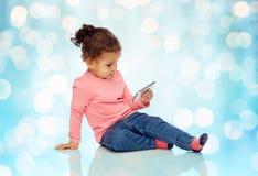 Piccola neonata sorridente che gioca con lo smartphone Immagine Stock