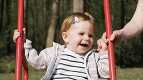 Piccola neonata sorridente sveglia che oscilla su un'oscillazione nel giorno di estate Movimento lento video d archivio