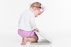Piccola neonata sveglia che gioca con il computer portatile. fotografia stock