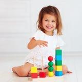 Piccola neonata sveglia che gioca con il giocattolo di legno sul pavimento fotografie stock libere da diritti