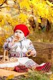 Piccola neonata sveglia che si siede sulla coperta nel legno. Immagine Stock Libera da Diritti