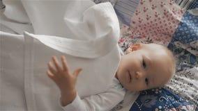 Piccola neonata sveglia sul letto che si nasconde e che gioca con gli strati video d archivio