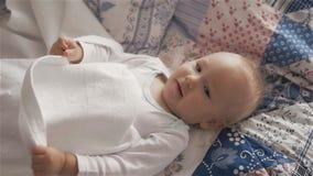 Piccola neonata sveglia sul letto che si nasconde e che gioca con gli strati archivi video
