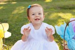 Piccola neonata sveglia in vestito bianco vicino al canestro di vimini con il GIF Fotografie Stock Libere da Diritti