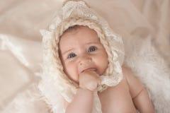 Piccola neonata, trovandosi sul letto, succhiante il suo pollice Immagini Stock