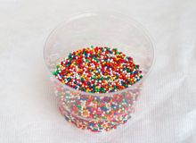 Piccola palla multicolore dello zucchero nella tazza di plastica per il forno fotografie stock libere da diritti