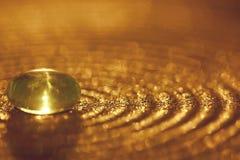 Piccola pietra di vetro su un piatto con le scintille e il bokeh dorati immagini stock libere da diritti