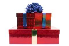 Piccola pila di contenitori di regalo rossi di Natale con l'arco del nastro blu isolato su fondo bianco Fotografia Stock Libera da Diritti