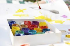 Piccola pittura dei bambini con le pitture e le spazzole su un grande strato sulla via un giorno soleggiato, una creatività e un  Fotografia Stock