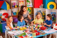 Piccola pittura del dito della ragazza degli studenti nella classe di scuola di arte Immagine Stock