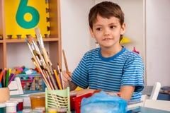 Piccola pittura del ragazzo degli studenti nella classe di scuola di arte Immagine Stock