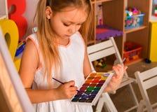 Piccola pittura della ragazza dello studente nella classe di scuola di arte Immagini Stock