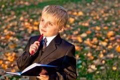 Piccola pupilla del ragazzo con la matita ed il taccuino Fotografia Stock