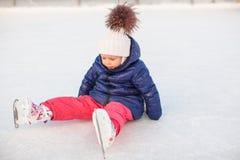 Piccola ragazza adorabile che si siede sul ghiaccio con i pattini Fotografie Stock