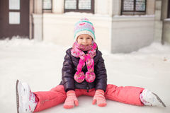 Piccola ragazza adorabile che si siede sul ghiaccio con i pattini Fotografie Stock Libere da Diritti