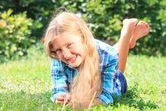 Piccola ragazza adorabile che si trova sull'erba fotografie stock libere da diritti