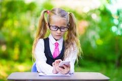 Piccola ragazza adorabile della scuola ad una tavola con le note Fotografia Stock Libera da Diritti