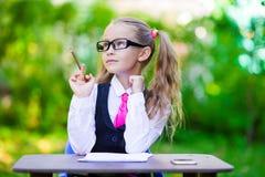 Piccola ragazza adorabile della scuola ad una tavola con le note Immagine Stock