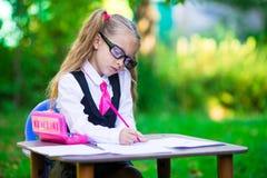 Piccola ragazza adorabile della scuola allo scrittorio con le note e Immagine Stock