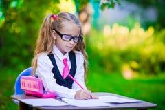 Piccola ragazza adorabile della scuola allo scrittorio con le note e Fotografie Stock Libere da Diritti