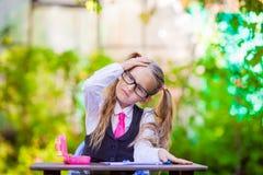 Piccola ragazza adorabile della scuola allo scrittorio con le note e Fotografia Stock Libera da Diritti