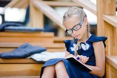 Piccola ragazza adorabile della scuola con le note e le matite all'aperto Di nuovo al banco Fotografia Stock