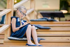 Piccola ragazza adorabile della scuola con le note e le matite all'aperto Di nuovo al banco Immagini Stock Libere da Diritti