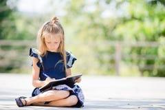 Piccola ragazza adorabile della scuola con le note e le matite all'aperto Di nuovo al banco Fotografie Stock