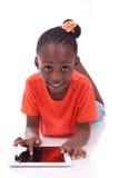 Piccola ragazza afroamericana che per mezzo di un pc della compressa Immagine Stock