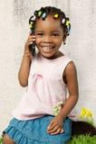 Piccola ragazza afroamericana che per mezzo di un telefono cellulare Fotografia Stock