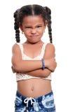 Piccola ragazza afroamericana con un fronte arrabbiato isolato su bianco Immagine Stock